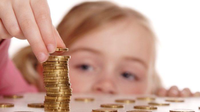 ребенок складывает деньги в стопку