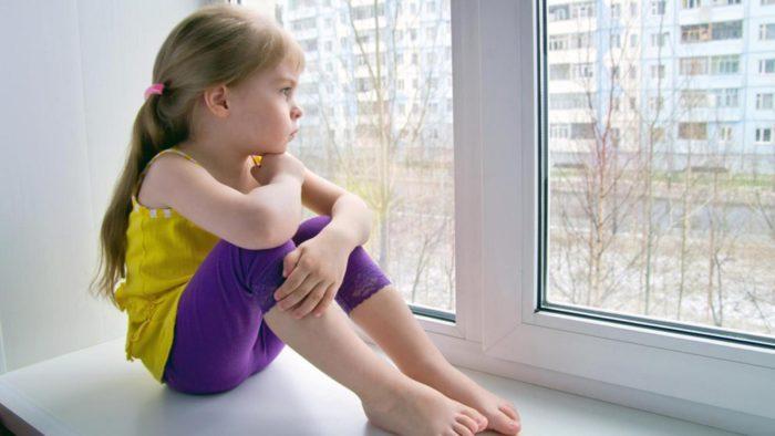 несовершеннолетний ребенок сидит на подоконнике