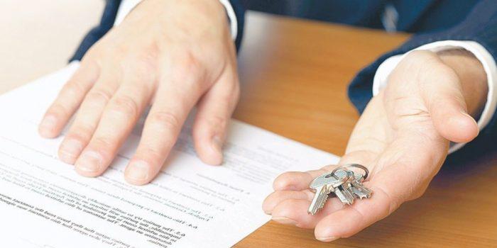 связка ключей в руках и документ на столе