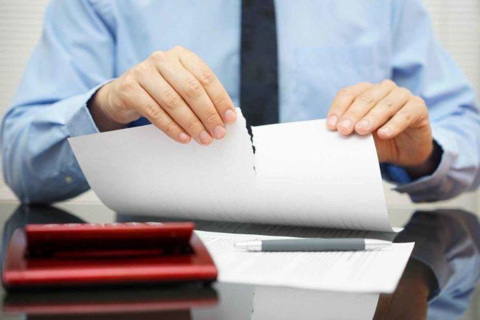 разорванный в руках документ, ручка с бумагами и калькулятором на столе