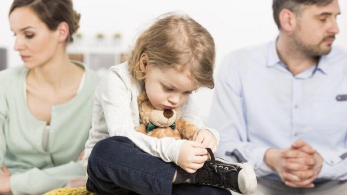 родители и ребенок по центру сидят на диване