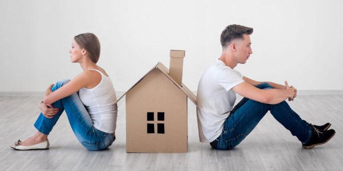 парень и девушка сидят спинами к маленькому домику из картона