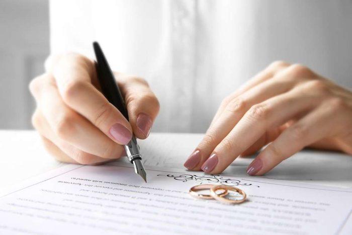 обручальные кольца и брачный контракт на столе