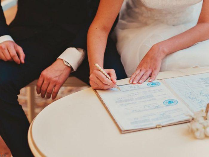 жениъ и невеста подписывают документ
