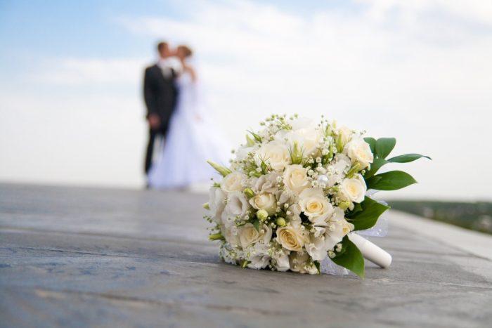 свадебный букет и жених с невестой на фоне