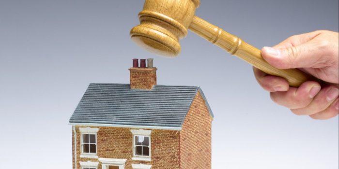 судейский молоток в руке и маленький домик