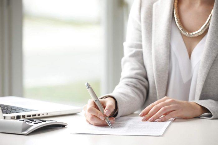 женщина заполняет документы ручкой, калькулятор и ноутбук на столе