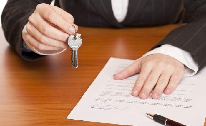 связка ключей в руках, документ и ручка на столе