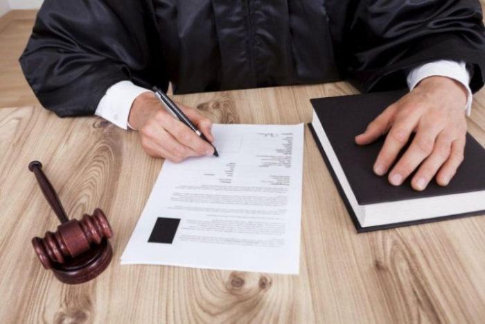 заполнение документов судьей, книга и судейский молоток на столе
