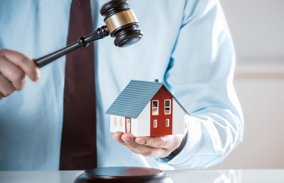 судейский молоток и декоративный домик в руках человека в рубашке с галстуком