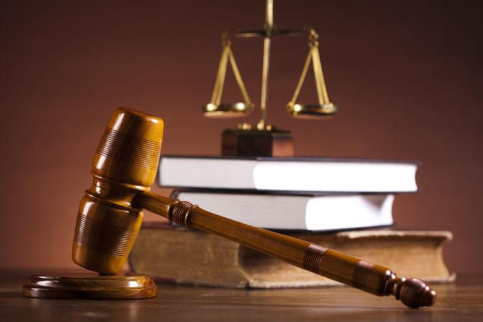 молоток судьи и книги на столе, судейские весы на фоне