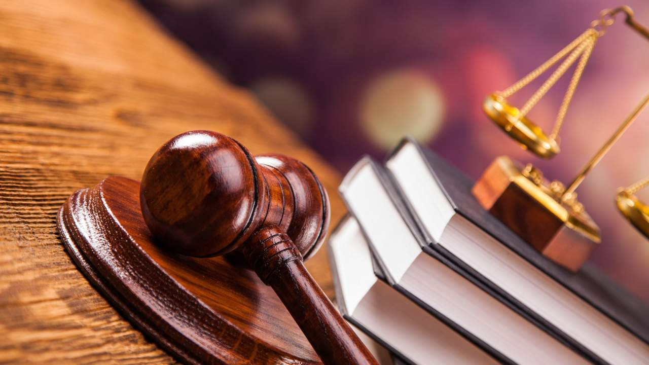 судейский молоток и стопка книг на столе