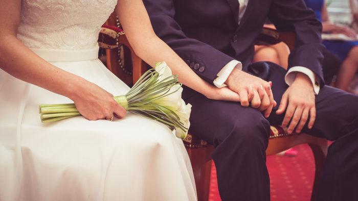 девушка в белом платье держит свадебный букет и рядом сидит мужчина сидит в костюме