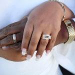 руки со светлой и темной кожей с обручальными кольцами