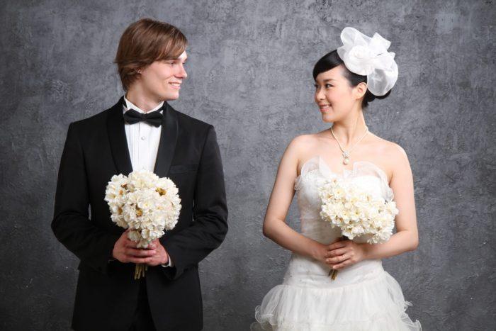 невеста корейской национальности и жених держат свадебные букеты