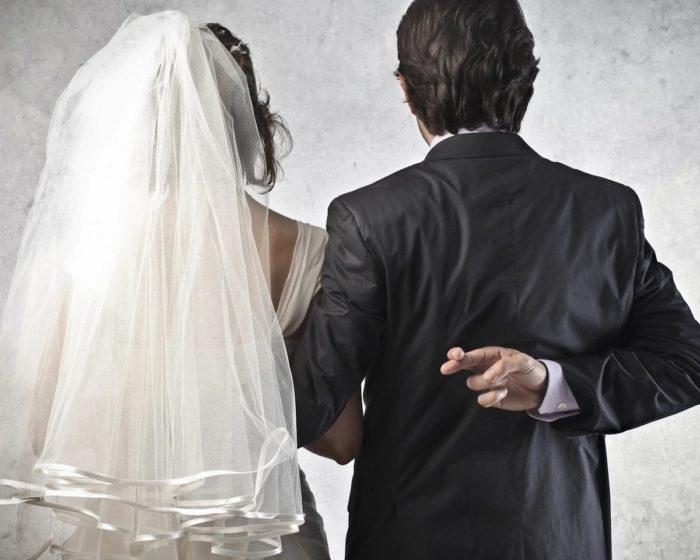 невеста в белом платье и жених в костюме перекрестил пальца за спиной