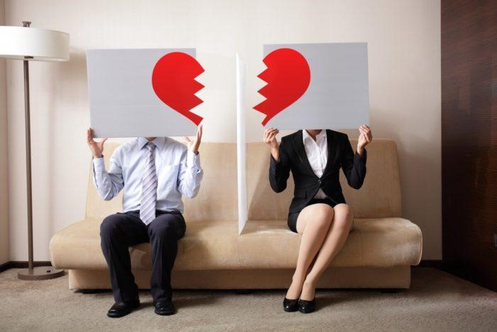 мужчина и женщина сидят на диване и держат таблички с половинками сердец
