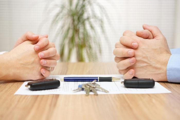 руки на столе, документ, ручка, связка клюей и брелки от машины