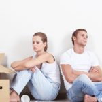 девушка с парнем сидят возле стены в доме с коробками