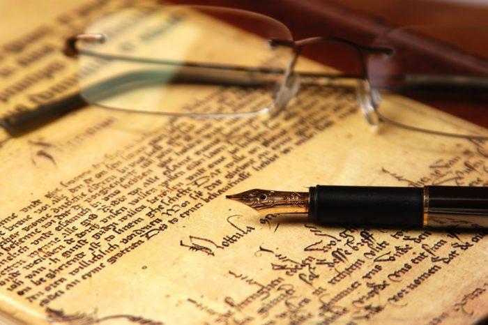 перьевая ручка и очки на документе