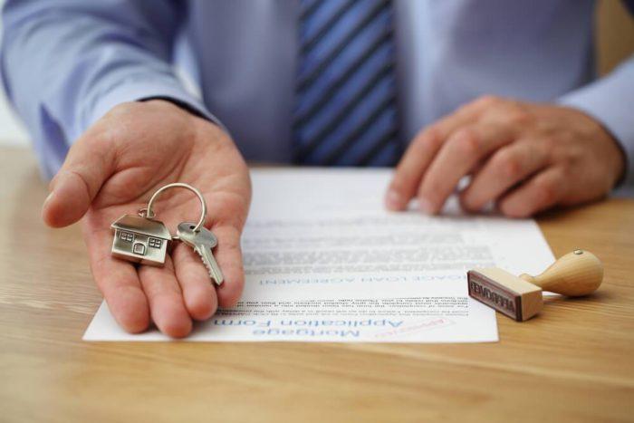 ключ с брелком на ладони человека, печать и документы на столе