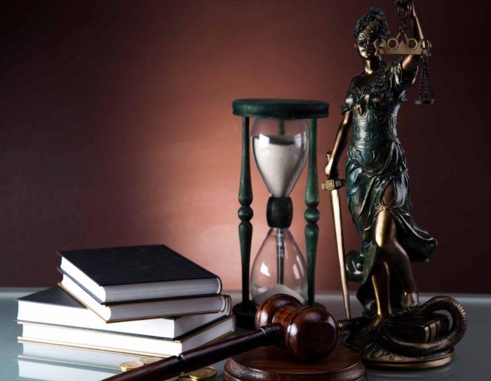 статуя правосудия, книги, песочные часы и судейский молоток на столе