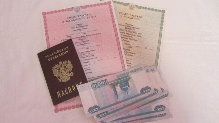 свидетельство о заключении брака, свидетельство о рождении, российский паспорт и деньги на столе