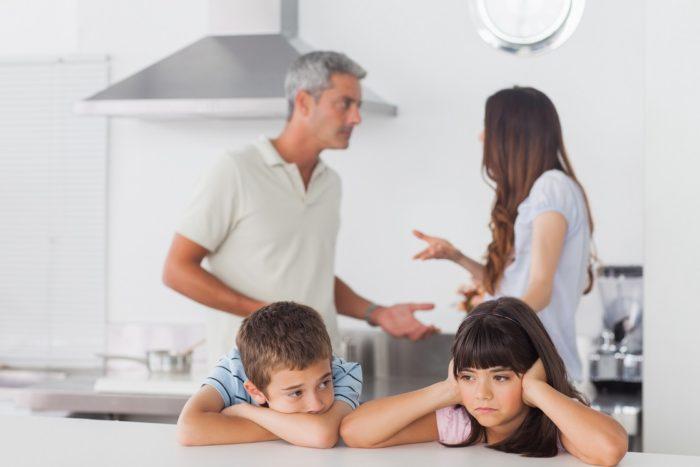 мальчик и девочка за столом на кухне, ссора родителей на фоне