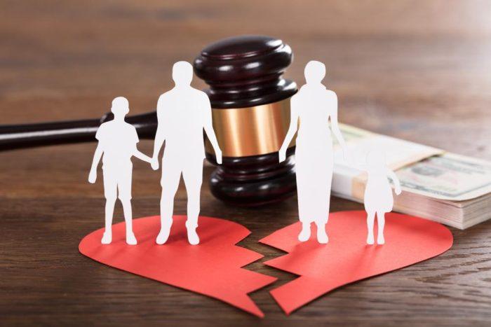 изображенная семья с детьми, судейский молоток и две половинки бумажного сердца на столе