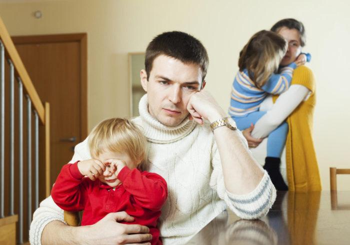 отец с ребенком на руках и мать с ребенком на фоне