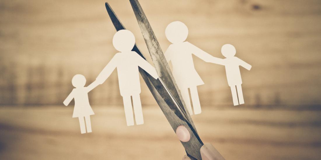 вырезанные из бумаги фигуры семьи и ножницы