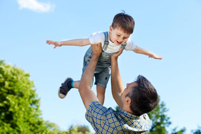 отец подкидывает маленького мальчика к верху
