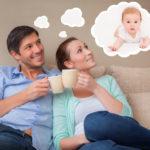 семья сидит на диване с кружками и мечтает о ребенке
