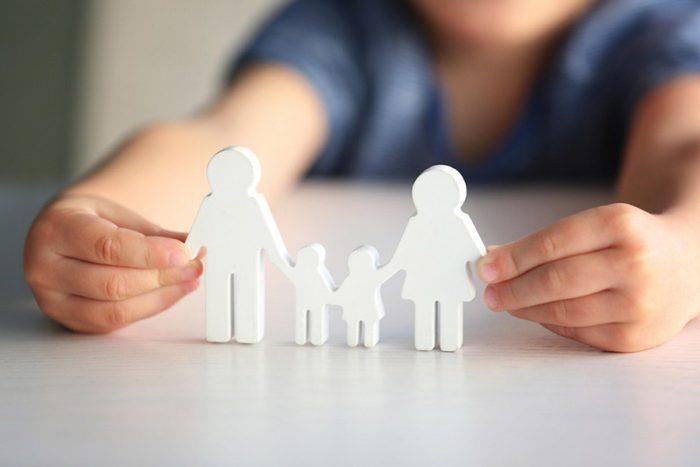 семья из белых фигурок на столе в детских руках