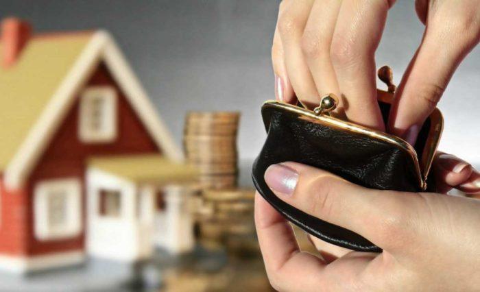 черный кошелек и декоративный домик с деньгами на фоне