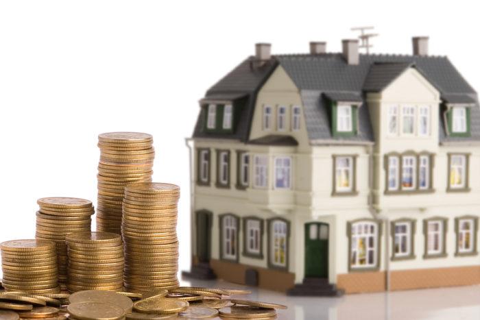 декоративный трехэтажный дом и стопки железных денег