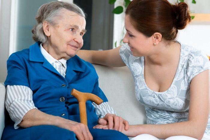 пожилая женщина с палочкой и ее опекун на диване
