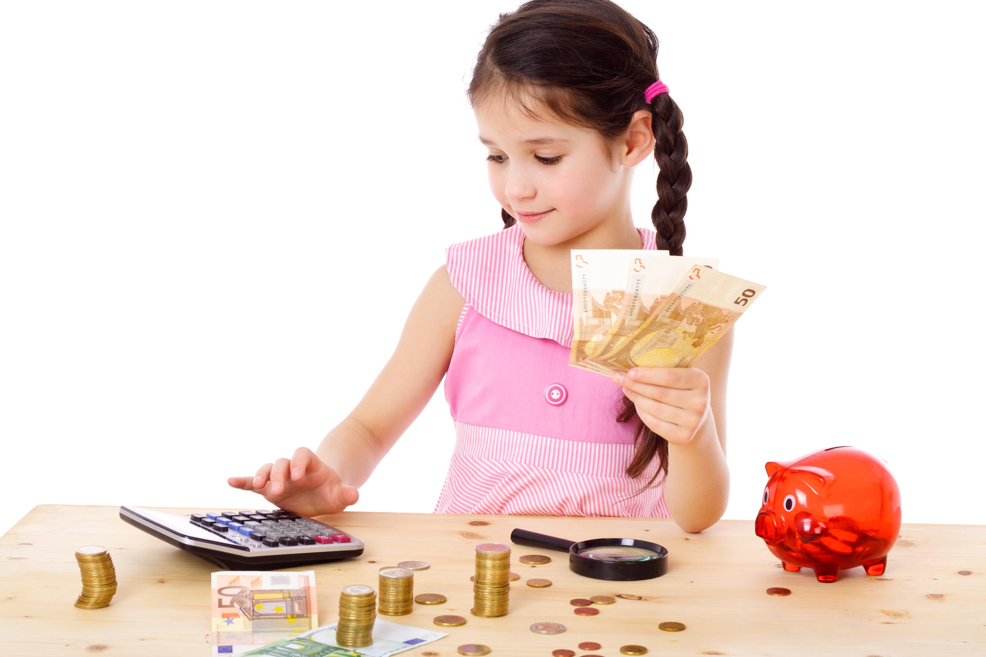 девочка держит деньги в руке и считает на калькуляторе, деньги, копилка и лупа на столе