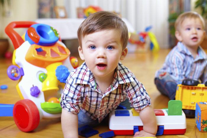 маленькие дети играют игрушками на полу