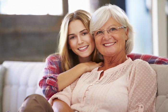 пожилая женщина и взрослая дочь сидят на диване