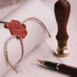 сверток бумаги, скрепленный печатью, перьевая ручка и документы на столе