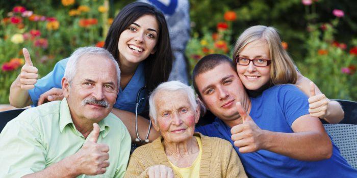 пожилые женщина и мужчина и взрослые дети фотографируются с выставленным большим пальцем