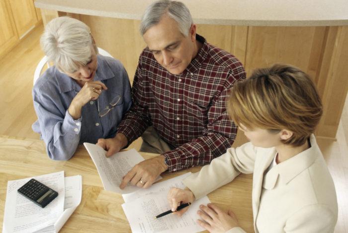 пожилая пара рассматривает документы с юристом