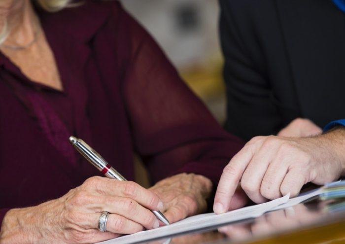 пожилая женщина подписывает документ ручкой