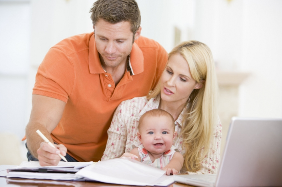 мать с ребенком на руках и отец заполняет отчет опекуна