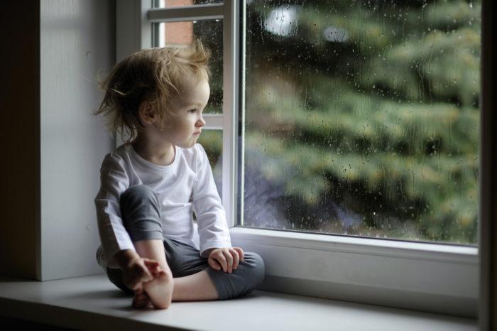 маленький ребенок сидит на подоконнике