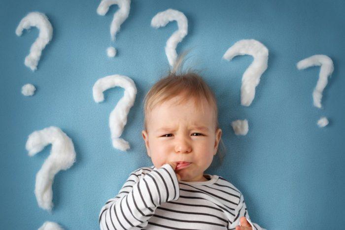 маленький ребенок и вопросительные знаки на стене