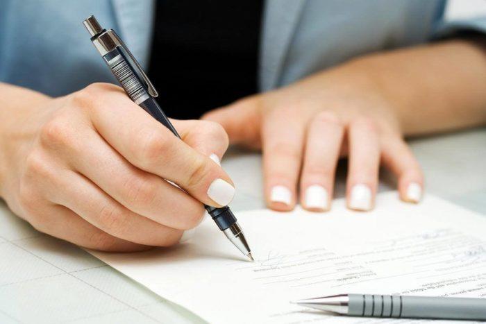 заполнение заявления на столе ручкой