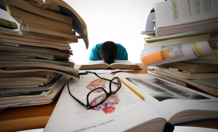 стопки книг и журналов с ручкой и очками на столе