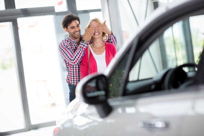 парень закрывает девушке глаза, стоя перед машиной